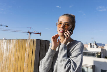 Young woman using smartphone on an urban rooftop terrace - VABF02198