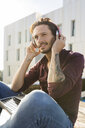 Man on a rooftop terrace, listening music with his headphones - VABF02213
