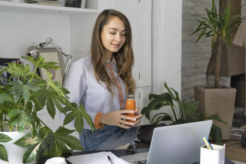 Young businesswoman working from home, taking a break, drinking juice - ERRF00619