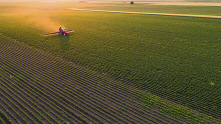 Serbia, Vojvodina, Aerial view of a tractor spraying soybean crops - NOF00076