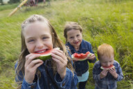 Girls and boy eating watermelon in field - HEROF04667