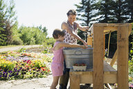 Mother and daughter rinsing fresh picked berries - HEROF04688