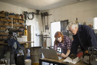 Father and daughter working on laptop in workshop - HEROF04760