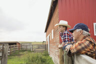 Grandfather and grandson leaning on fence on farm - HEROF04778