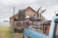 Multi-generation men loading logs onto truck on farm - HEROF04781