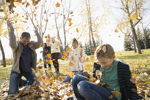 Family playing throwing autumn leaves in sunny park - HEROF04931