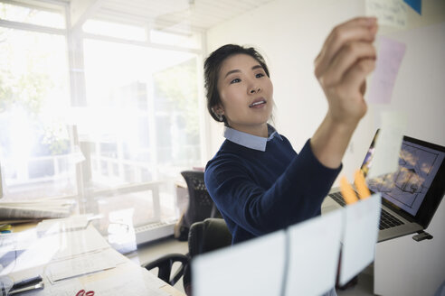 Female architect brainstorming with adhesive notes and laptop at office glass - HEROF04955