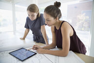Female architects meeting reviewing digital blueprint on digital tablet in office - HEROF04979