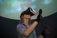 Girl using virtual reality simulator in science center theater - HEROF04997