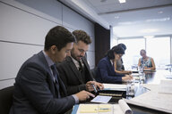 Businessmen using digital tablet in conference room meeting - HEROF05024