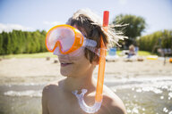 Close up smiling boy with snorkel in sunny summer lake - HEROF05069