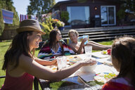 Family eating at sunny summer patio table - HEROF05072