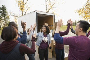 Enthusiastic volunteers high fiving outside truck - HEROF05147