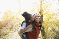 Daughter kissing mother in autumn woods - HEROF05153