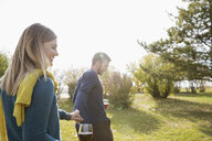 Couple holding hands drinking red wine in sunny autumn park - HEROF05156