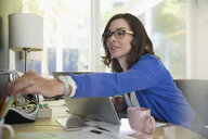 Businesswoman at laptop reaching for pen at desk - HEROF05159