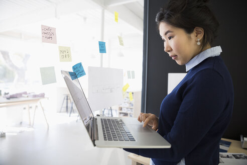 Businesswoman with laptop and adhesive notes at office glass - HEROF05162