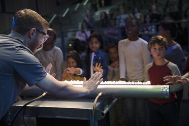 Children and scientist creating acoustic waves using a Rubens tube in science center theater - HEROF05180