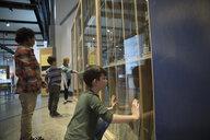 Curious boy watching exhibit display in science center - HEROF05192
