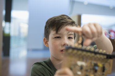Curious boy holding electronics piece in science center - HEROF05222
