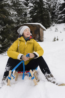 Austria, Tyrol, Thurn, content mature  woman sitting on sledge in the snow looking at distance - PSIF00212