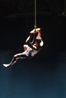 Mexiko, Yucatan, Tulum, man swinging on rope above a cenote - MMAF00760