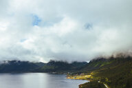 Clouds covering mountains by lake - ASTF02095