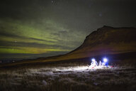 People with illuminated lighting equipments sitting on grassy field against mountain at night - ASTF02113