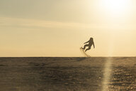Man with backpack jumping at the beach in the evening light - KBF00405