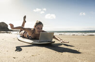 Young woman lying  on surfboard, using laptop - UUF16479