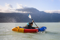 Woman packrafting, Howe Sound bay, Squamish, Canada - CUF47050