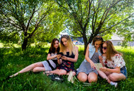 Girlfriends relaxing, using smart devices in city park - CUF47065