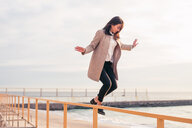 Woman jumping off handrail on beach - CUF47080
