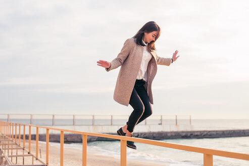 Woman jumping off handrail on beach - CUF47080