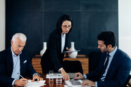 Businessmen and woman looking at charts and paperwork at boardroom table - CUF47101