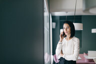 Young businesswoman in hotel making smartphone call - CUF47110