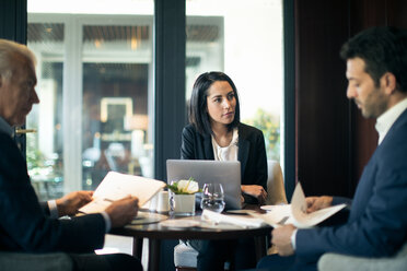 Businesswoman and men having meeting in hotel restaurant - CUF47119