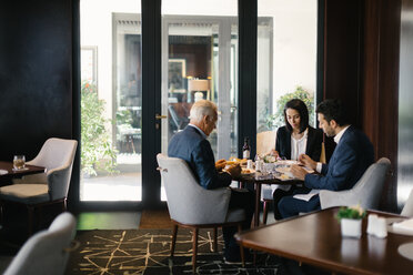 Two businessmen and woman having working lunch in hotel restaurant - CUF47122