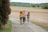 Friends running along by pushbike in countryside - CUF47197
