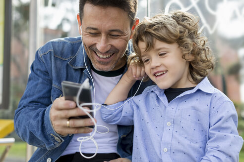 Happy father and son sharing cell phone and earbuds - MAUF02274