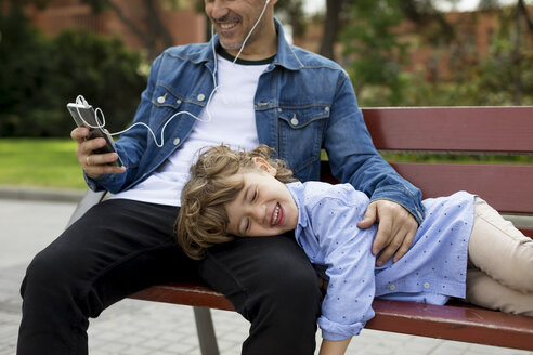 Happy father with son on a bench using cell phone and earbuds - MAUF02277