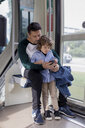 Father and son using cell phone in a tram - MAUF02286