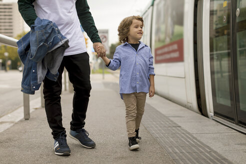 Father and son walking hand in hand at tram stop in the city - MAUF02292
