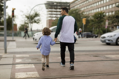 Rear view of father and son walking hand in hand in the city - MAUF02295