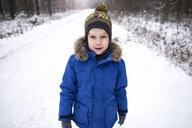 Portrait of little boy enjoying walk in winter forest - ABIF01124