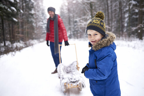 Portrait of smiling little boy in winter with his father and sledge - ABIF01127