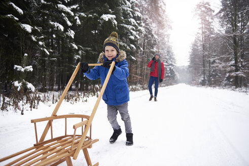 Little boy pushing sledge in winter forest while his father watching him from background - ABIF01130