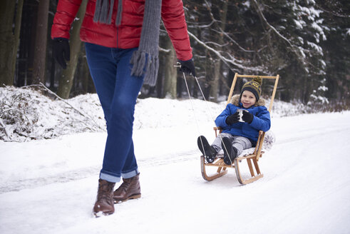 Smiling little boy drinking tea while his father pulling sledge - ABIF01136