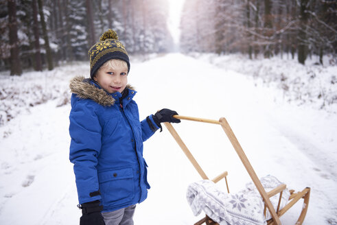 Portrait of smiling little boy with sledge in winter forest - ABIF01139