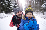 Portrait of father and little son together in winter forest - ABIF01148